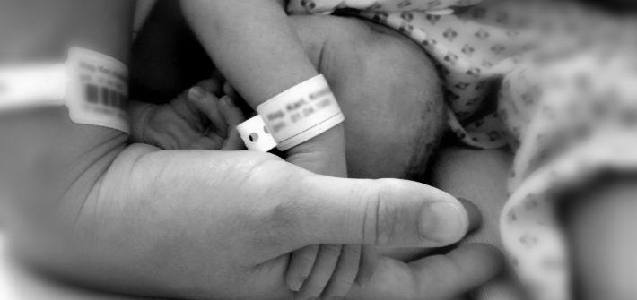 Neugeborenes hält die Hand der Mutter